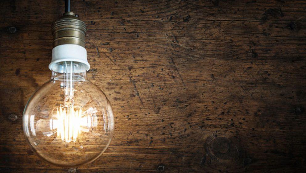 A lit lightbulb hanging against a wood panel.