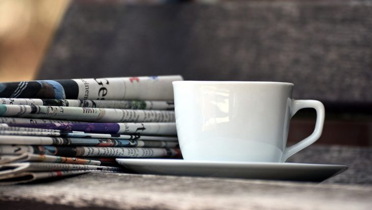 Newspaper with Coffee Cup