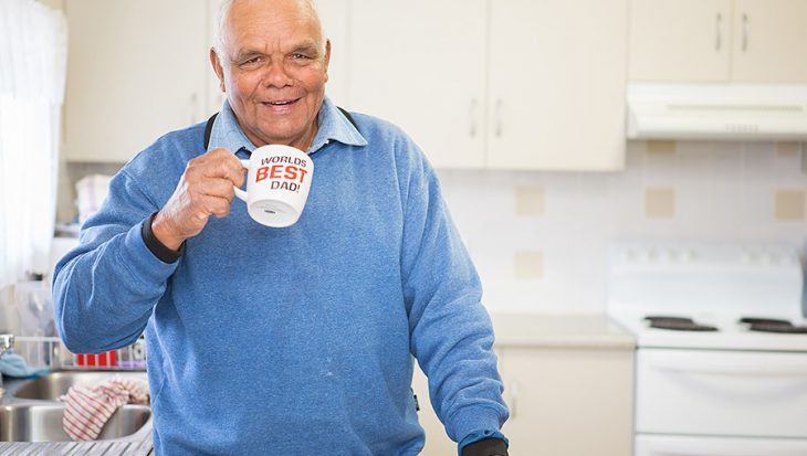 Financial resilient man drinking tea in kitchen